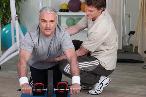 Mature man training with fitness coach small
